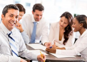 man-smiling-in-white-shirt-and-tie-near-other-workers-in-white